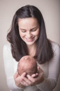 rochester ny newborn photographer captures mom smiling at new baby