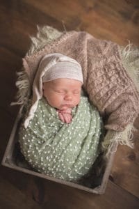 rochester ny newborn photographer captures baby sleeping in sleepy cap