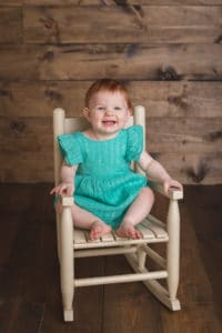 rochester ny baby photographer captures little girl sitting in a rocking chair
