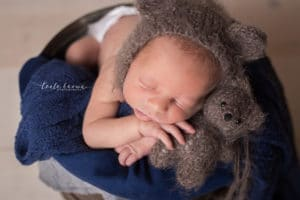newborn photographer in rochester ny captures newborn sleeping with teddy bear
