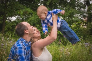 rochester ny family photographer captures parents holding baby up in the air