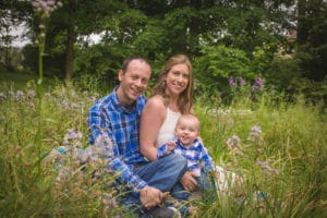 family photographer in rochester ny captures parents and baby smiling in a field