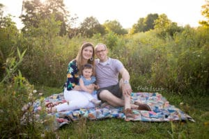 family photographer in rochester captures family sitting on a quilt smiling