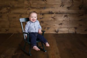 baby photographer in rochester ny captures baby in a rocking chair smiling