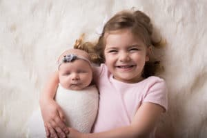family photographer in rochester, ny captures big sister holding her newborn baby sister