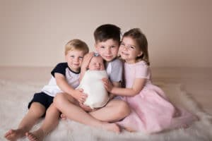 family photographer in rochester, ny captures brothers and sisters snuggling newborn baby sister