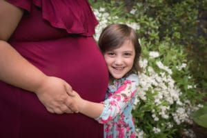 maternity photographer in rochester, ny captures big sister hugging the belly ofexpectant mom