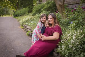 maternity photographer in rochester, ny captures expectant mom hugging her kids