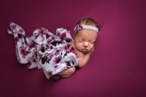 newborn photographer in rochester ny captures baby girl sleeping with floral blanket