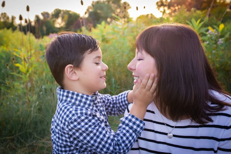 family photographer in rochester ny captures family playing and smiling together in the setting sun