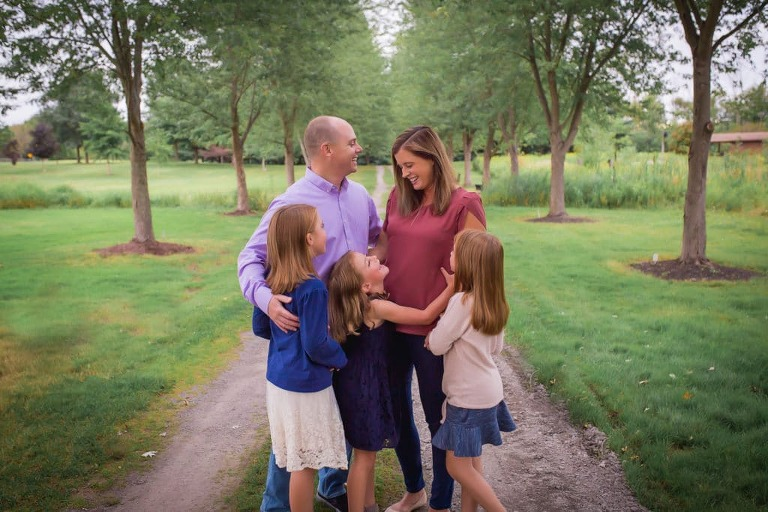 family photographer in rochester ny captures family smiling and laughing together in Tinker Park