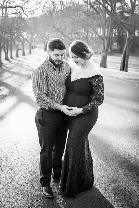 maternity photographer in rochester ny captures expectant mom wearing a red lace maternity gown at sunset