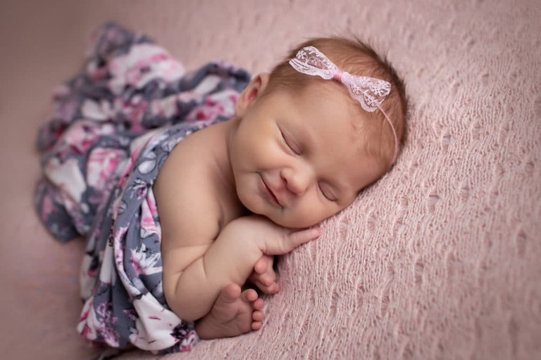 newborn photographer in rochester ny captures newborn baby girl in pink and floral