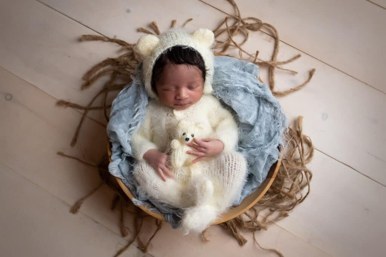 newborn photographer in rochester ny captures newborn baby boy sleeping in teddy bear outfit
