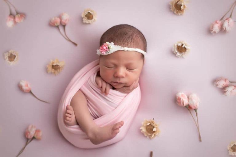 newborn photographer in rochester ny captures newborn baby girl sleeping among the flowers