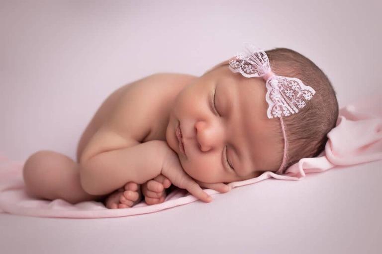 newborn photographer in rochester ny captures newborn baby girl sleeping in womb pose