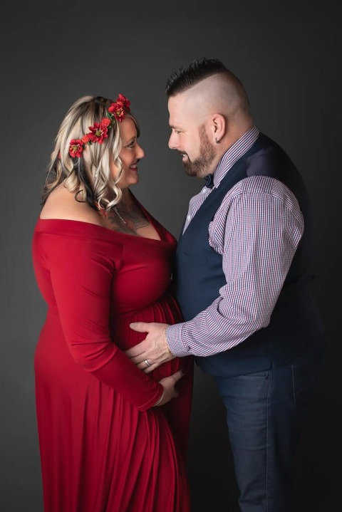 rochester ny maternity photographer captures pregnancy portraits for expectant mom wearing a gorgeous red gown