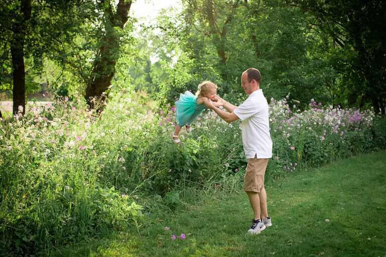 family photographer in rochester ny captures family playing together at sunset in the wildflowers